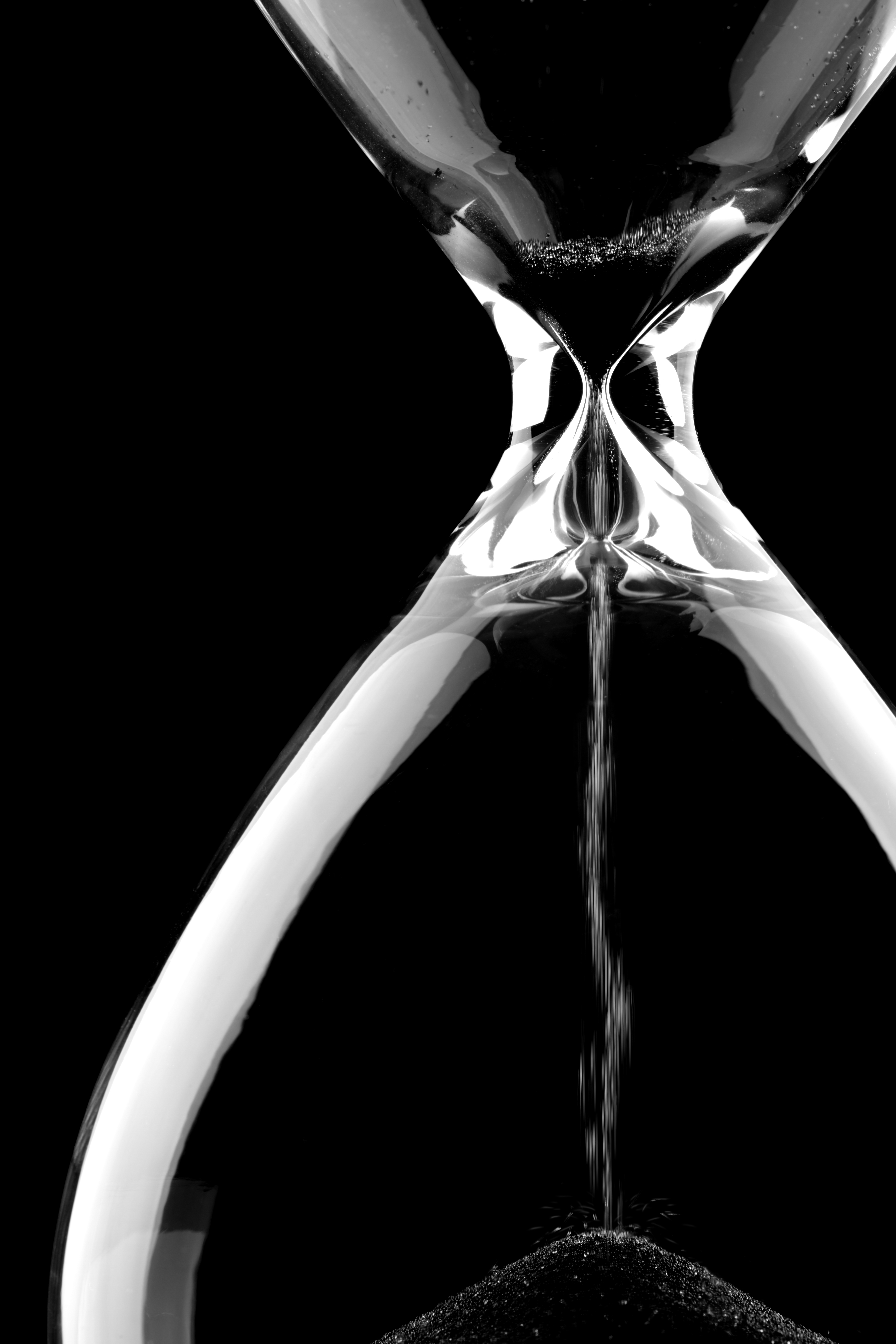Sand flowing through an hourglass on black background concept for time running out